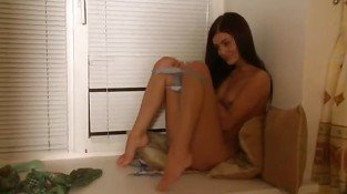 brunette making strip in her room